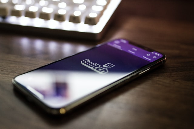 phone sitting on table with twitch logo