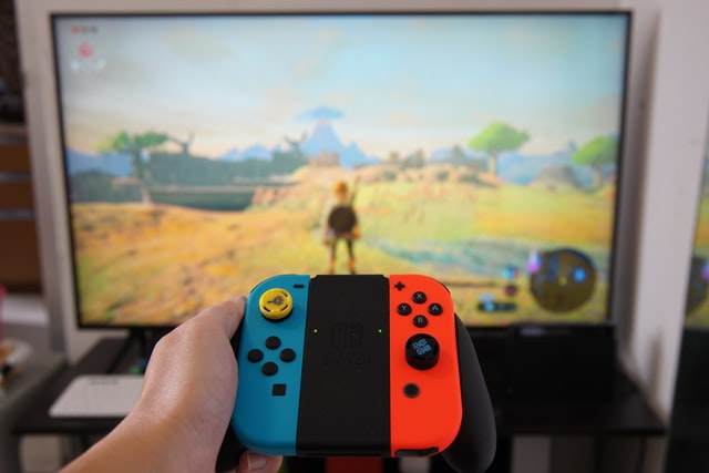 nintendo switch controller with a tv in the background